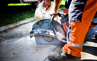 Construction worker cutting Asphalt pavi