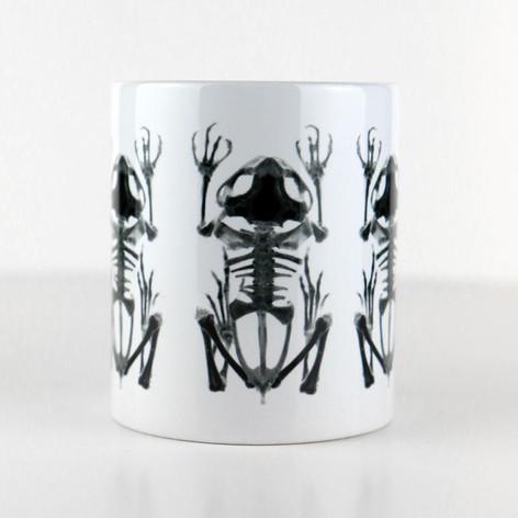 Tasse blanche avec trois squelettes de grenouille  DISPONIBLE  Quantité : 6 Prix : 15€ Réf : DIV02  Envoi possible, frais de port en sus, 6€ par La Poste ou 4,50€ par Mondial Relay