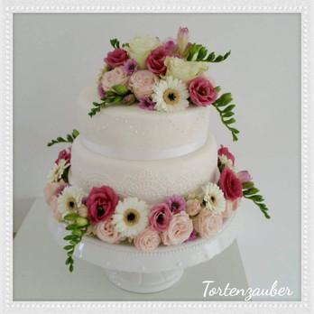 Blumige Hochzeitstorte mit essbarer Spitze
