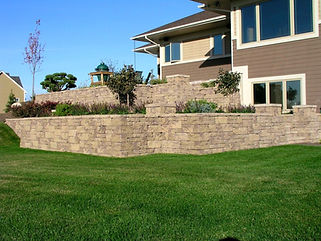 Retaining wall in front of house with lawn