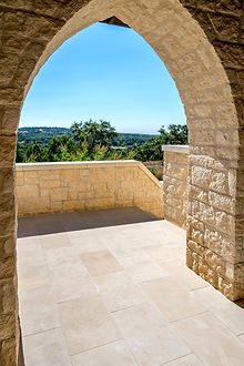 Stone archway overlooking trees, stairs and sky