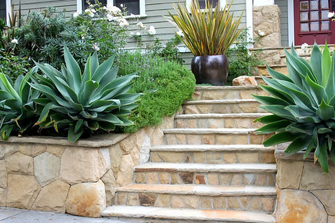 Stone steps and sandstone wall in front of house with landscaping features