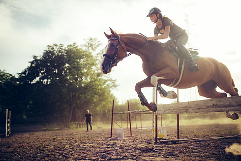 Young female jockey on horse leaping ove
