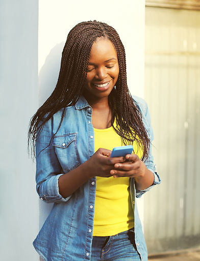 Happy smiling african woman holding phone in city.jpg