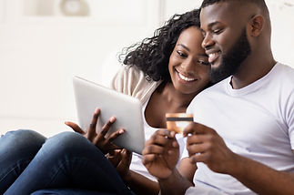 Cheerful Black Spouses Shopping Online Using Digital Tablet At Home, Entering Credit Card