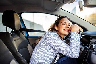 Happy woman hugging her steering wheel.