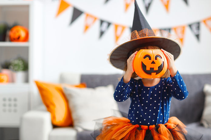 Happy laughing child girl in witch costume.