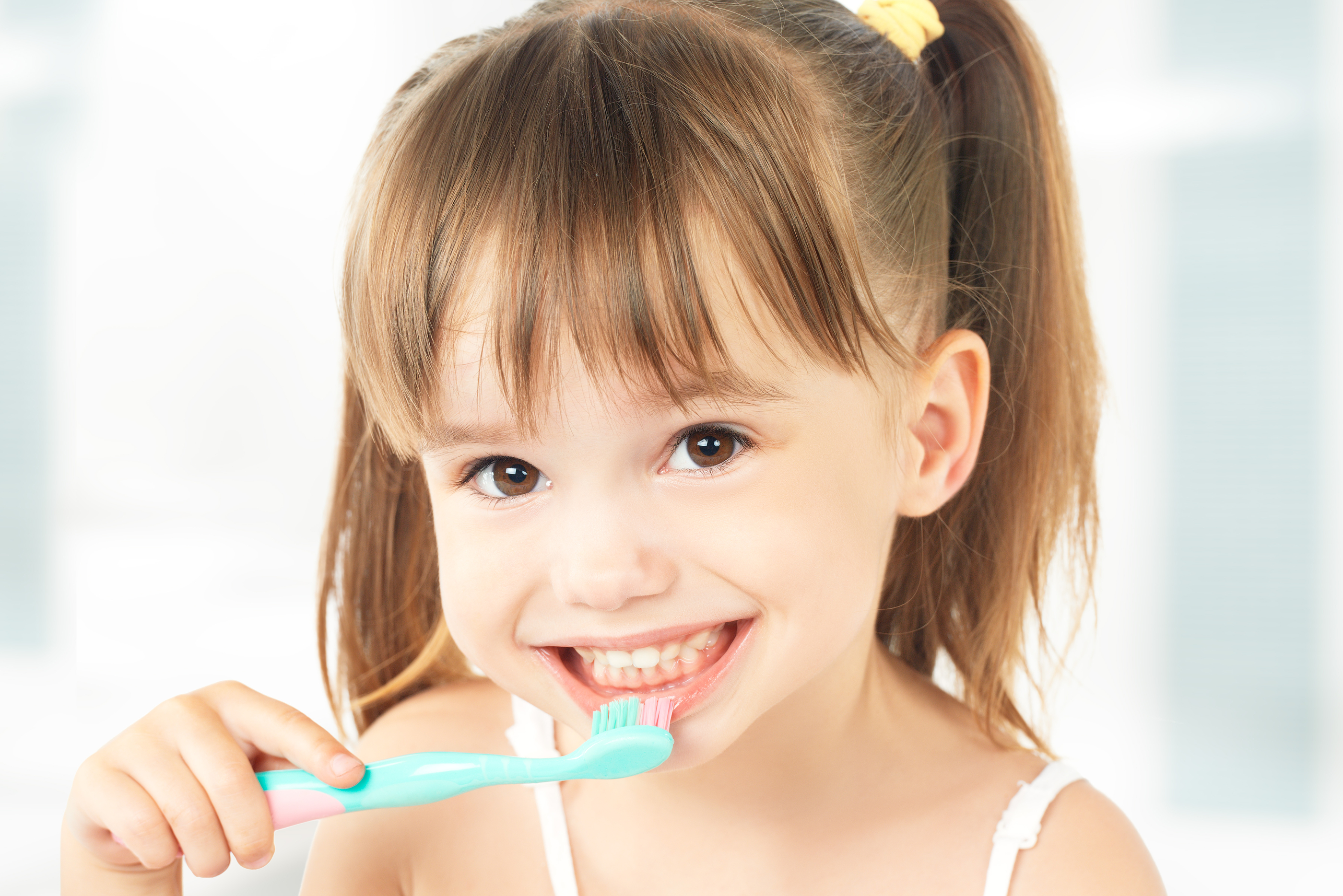 happy little girl brushing her teeth.jpg