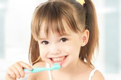 happy little girl brushing her teeth.jpg
