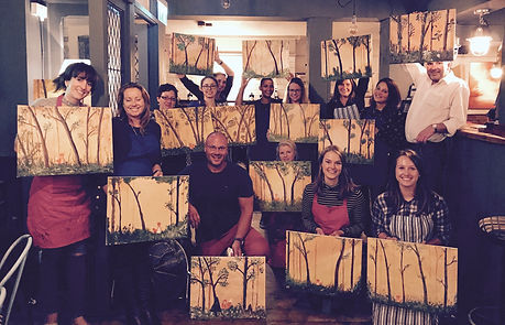 A group of artists holding paintings they have created.