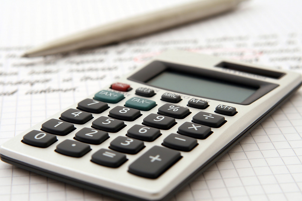 A calculator and pen resting atop financial paperwork.