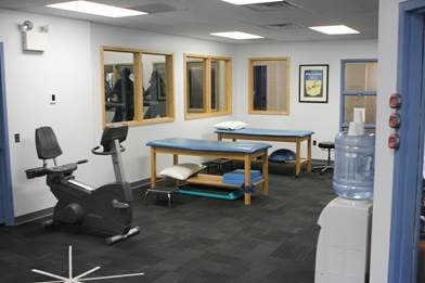 A physical therapy room with equipment and tables.