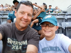 A child and mentor sitting in the stands of a Philadelphia Eagles football game.