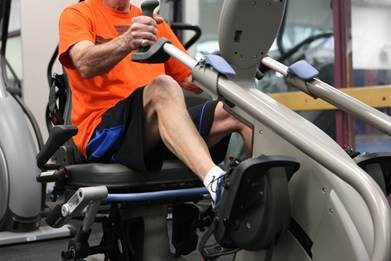 A man using exercise equipment with pedals.