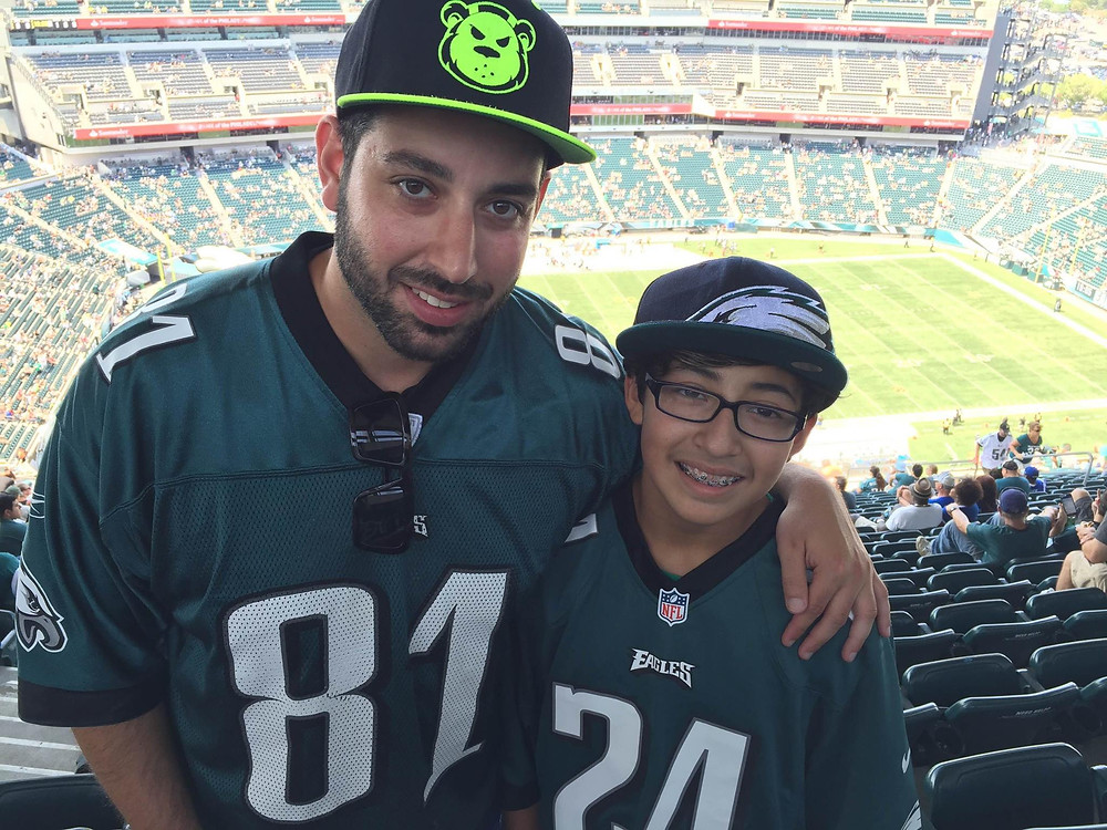 A child and mentor duo at a Philadelphia Eagles football game.