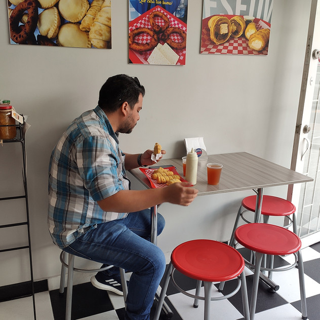 Cliente disfrutando de la comida de Pastelitos Edward (tequeños, pastelitos) y papelón de bebida.