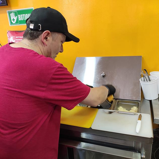 Personal rallando el queso amarillo para poder preparar las arepas.