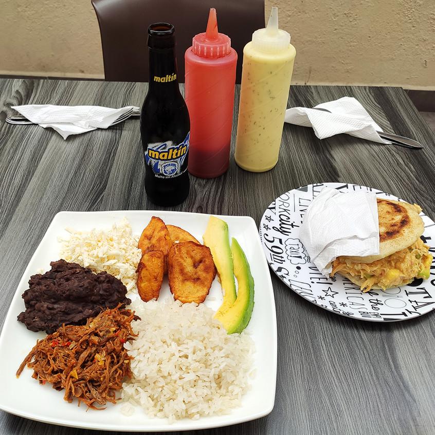 A la izquierda el plato típico Pabellón (arroz, carne mechada, caraotas, tajadas, queso blanco y aguacate), a la derecha la arepa de reina pepiada (pollo mechado y aguacate).