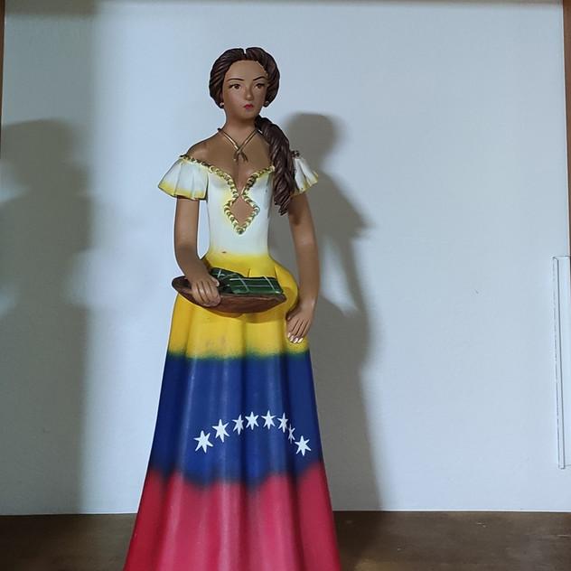 Muñeca con un vestido de los colores de la bandera de Venezuela sosteniendo una bandeja de Hallacas.