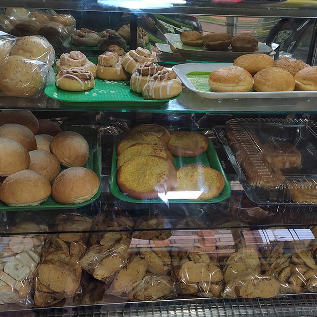 Variedad de panes: pan dulce, rollos de canela, golfeados, pan canilla rebanado, pan integral rebanado)