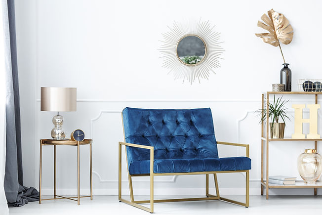 Blue bench between gold table with lamp and shelves with leaves in glamor living room inte