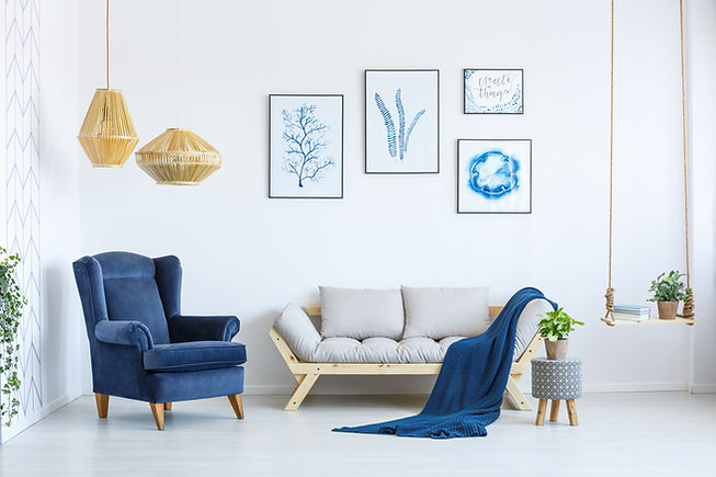 White sofa and blue armchair in living room with posters on the wall.jpg