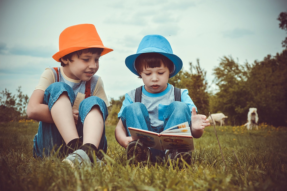 two boys reading a book in a grass field