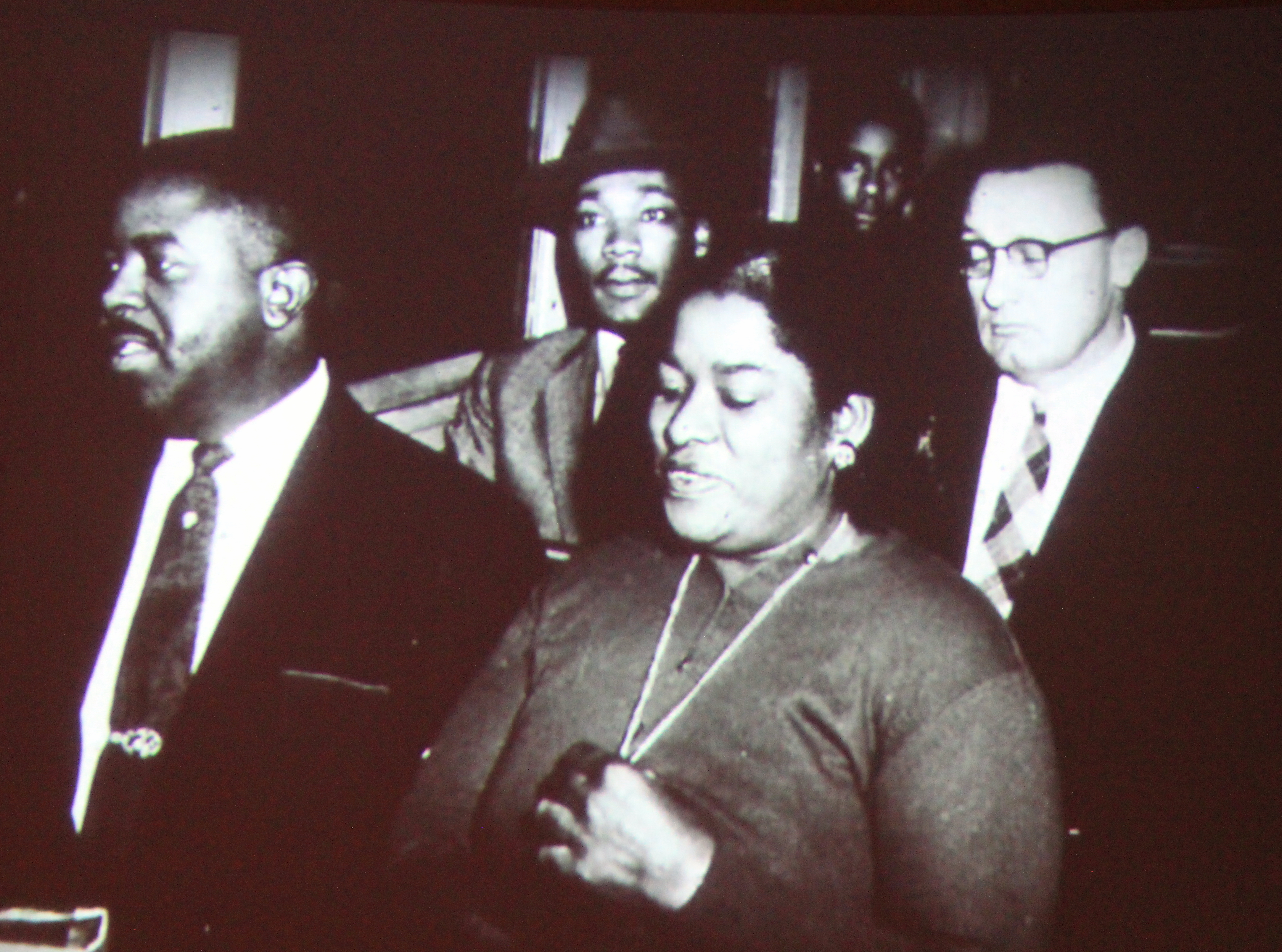Martin Luther King, Jr. sits on a bus next to a white man