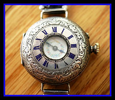 English Hallmarked (Birmingham) - Fancy Engraved Sterling Silver Demi Case - Ladies Wristlet - 33 mm Across and 44 mm Lug to Lug - Enamel Outer Roman Numerals - Fancy Porcelain Dial - Silver Fancy Bracelet - and in Fantastic Overall Condition (circa 1884)