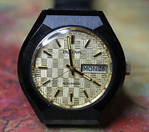 Bulova - Featuring a Very Unusual Gold Toned and Textured Finish Checker Board Dial with a Day and Date Function and a Black Case - Wristwatch - (circa 1976)