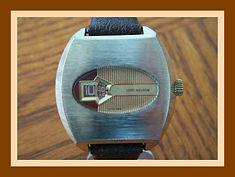 Lord Nelson - Jump Hour Wristwatch with an Oval Shaped Crystal, Gold Toned Brush Metal Case, and Brown and Gold Color Coordinated Dial - (circa 1960s)