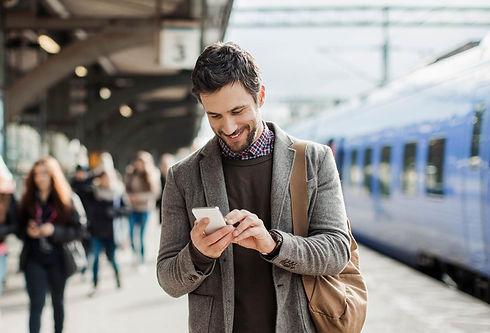 Man checking phone at train station