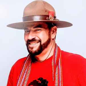 A headshot of an Indigenous man with a dark beard, wearing an antique boy scout leader's hat, a red Hudson's Bay Métis sash from 1870 around his neck, and a red t-shirt with Métis leader Louis Riel. Image taken in the photo studios at Banff Centre for Arts and Creativity