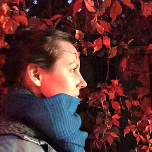 A woman with a fair complexion and swept back medium brown hair has a neutral expression. She is in profile facing right, looking into the distance. White light illuminates the front of her face. A thick blue scarf is wrapped around her neck and covers her chin. In the background is a wall of red leaves
