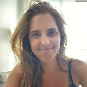 A close-up of a 28-year-old Latina woman with honey-coloured eyes and long, light-brown hair. She is smiling and wearing a sleeveless dark shirt