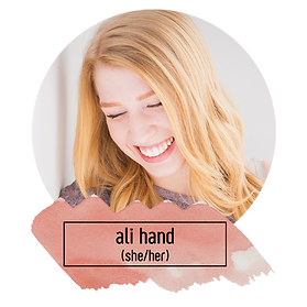 A close up of a white woman with long, blonde, loosely curled hair, wearing a purple sweater, in front of a white wall, smiling broadly and looking down. Underneath is written: Ali Hand (she/her).