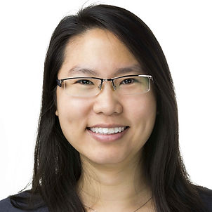 A photo of Philiz, a Southeast Asian woman who has a disability, looking at the camera with a radiant smile. She has straight dark hair and is wearing glasses, a white blouse, and a light grey suit jacket with a white background