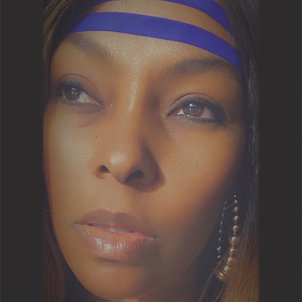 Keze, not looking directly at the camera, wearing gold hoop earrings and a blue headband across the forehead