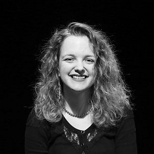 A black and white photo of a white woman with fair, curly hair. She is smiling
