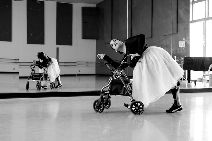 A black and white photograph of Vanessa dancing with her rollator (walker). She is leaning onto her walker with one arm gently leaning on the handle and the other arm leaning on the backrest. Her serene face is gently looking out into the distance. Her legs are positioned in a mid-walking stance. One of her leg braces is visible. Her hair is pulled back into a ballet bun. She is wearing a tulle dress; dark top, light and fluffy skirt. She is in a well lit dance studio where mirrors are visible and her reflection is present.