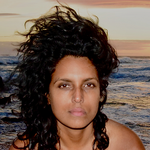 A photo of TextaQueen looking straiht at the camera. Their hair is blowing in the wind as waves crash behind them