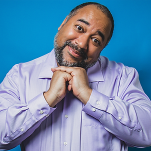 An image of a Black man from the elbows up, holding his hands under his chin; his head slightly tilted and bearing a loving smile. He wears a lavender shirt. The background is a gradient blue