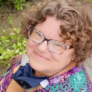 A close up of a smiling white woman with curly brown hair, blue eyes, and glasses with frames that have splashes of blue, pink, and yellow. Kim is looking up at the camera and is wearing a purple, green, and coral sleeveless summer blouse. There is green foliage on the ground