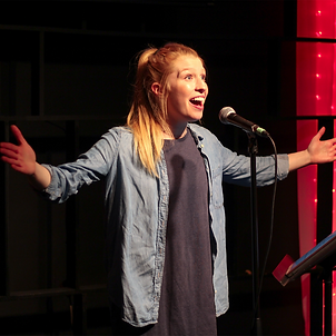 A waist-up photo of a white woman with blue eyes and long blonde hair in a high ponytail. She is smiling broadly with her arms outstretched, singing into a microphone on a small stage, wearing a dark blue t-shirt dress and a denim shirt