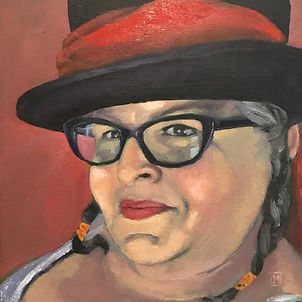 A self-portrait painting of a mischievously smiling tan-skinned woman with dark brown eyes and black glasses. Her salt-and-pepper hair is in braided on either side and tied with an orange elastic. She is wearing a black top hat with a red scarf worn as a ribbon band