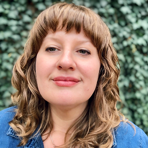 A woman with dark blonde curly hair and bangs is looking off to the left of the frame and smiling. She is wearing a denim shirt and behind her there is a wall of green leaves