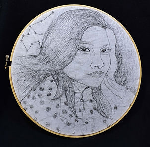 A self portrait of Asma, done in embroidery by using Asma's own hair on white fabric, with many black and white lines and circles and constellations, looking at the viewers, smiling