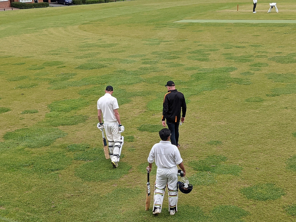 Glen and Susmit in whites walking towards the middle, speaking to Lachlan
