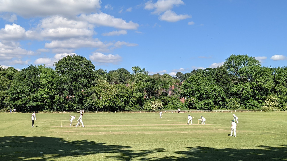 Side on view of cricket pitch, bowler delivering with Susmit in his stance
