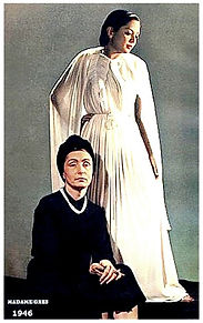 This is an image of Madame Alix Gres posed at the foot of a model wearing one of the gowns she designed  (circa 1946)